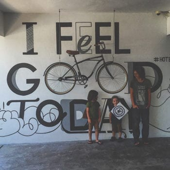 three boys stand in front of a wall that reads I feel good today